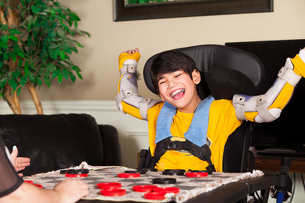 Young biracial disabled boy in wheelchair playing checkers at home.