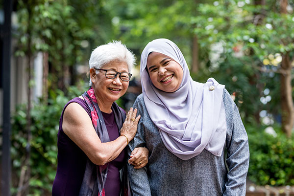 Image of senior woman with caregiver in the street.